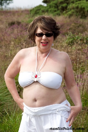 Gorgeous old babe with sunglasses wearing her all white dress and lingerie poses on a grassy field while slowly getting naked before she expose her huge boobs and nasty pussy. - XXXonXXX - Pic 4