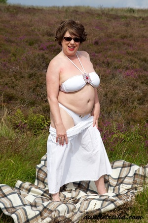 Gorgeous old babe with sunglasses wearing her all white dress and lingerie poses on a grassy field while slowly getting naked before she expose her huge boobs and nasty pussy. - XXXonXXX - Pic 6