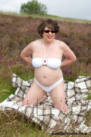 Gorgeous old babe with sunglasses wearing her all white dress and lingerie poses on a grassy field while slowly getting naked before she expose her huge boobs and nasty pussy. - XXXonXXX - Pic 9