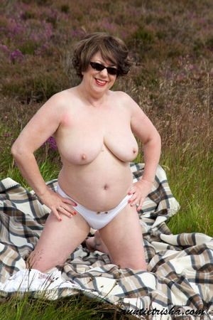 Gorgeous old babe with sunglasses wearing her all white dress and lingerie poses on a grassy field while slowly getting naked before she expose her huge boobs and nasty pussy. - XXXonXXX - Pic 11