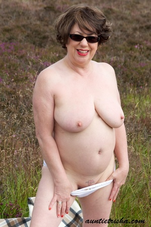 Gorgeous old babe with sunglasses wearing her all white dress and lingerie poses on a grassy field while slowly getting naked before she expose her huge boobs and nasty pussy. - XXXonXXX - Pic 13