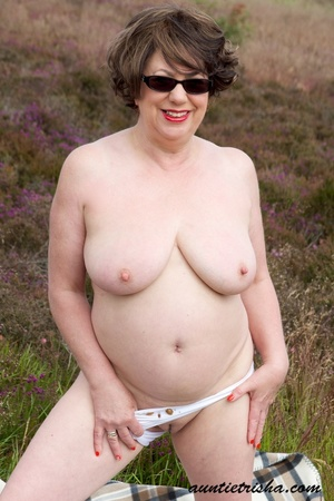Gorgeous old babe with sunglasses wearing her all white dress and lingerie poses on a grassy field while slowly getting naked before she expose her huge boobs and nasty pussy. - XXXonXXX - Pic 14