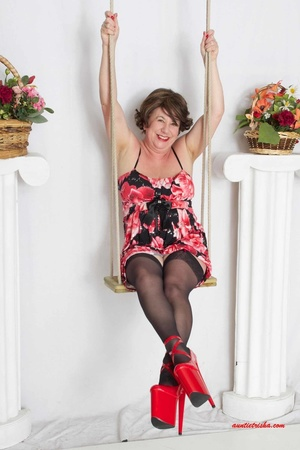 Sweet granny slowly peels off her black, red and white floral dress then reveals her giant boobs before she lets her pussy peek while she sits on a swing wearing her black stockings with black and pink suspenders and red high heels. - XXXonXXX - Pic 4