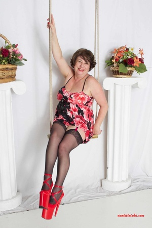 Sweet granny slowly peels off her black, red and white floral dress then reveals her giant boobs before she lets her pussy peek while she sits on a swing wearing her black stockings with black and pink suspenders and red high heels. - XXXonXXX - Pic 5
