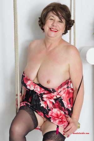 Sweet granny slowly peels off her black, red and white floral dress then reveals her giant boobs before she lets her pussy peek while she sits on a swing wearing her black stockings with black and pink suspenders and red high heels. - XXXonXXX - Pic 6