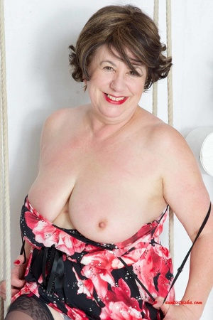 Sweet granny slowly peels off her black, red and white floral dress then reveals her giant boobs before she lets her pussy peek while she sits on a swing wearing her black stockings with black and pink suspenders and red high heels. - XXXonXXX - Pic 7