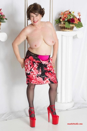 Sweet granny slowly peels off her black, red and white floral dress then reveals her giant boobs before she lets her pussy peek while she sits on a swing wearing her black stockings with black and pink suspenders and red high heels. - XXXonXXX - Pic 9