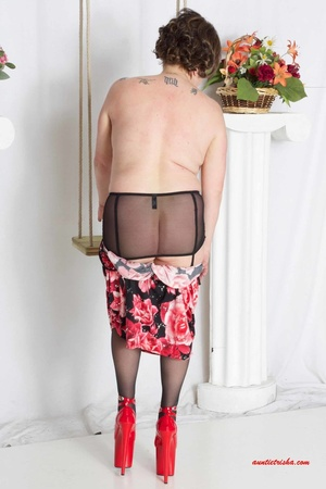 Sweet granny slowly peels off her black, red and white floral dress then reveals her giant boobs before she lets her pussy peek while she sits on a swing wearing her black stockings with black and pink suspenders and red high heels. - XXXonXXX - Pic 10