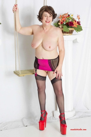 Sweet granny slowly peels off her black, red and white floral dress then reveals her giant boobs before she lets her pussy peek while she sits on a swing wearing her black stockings with black and pink suspenders and red high heels. - XXXonXXX - Pic 12