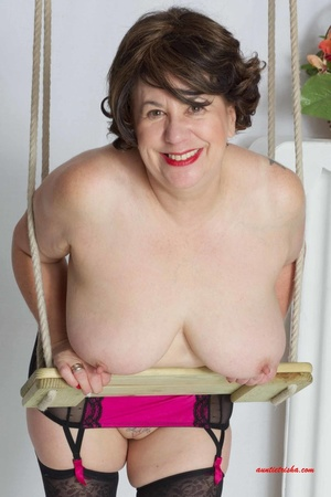 Sweet granny slowly peels off her black, red and white floral dress then reveals her giant boobs before she lets her pussy peek while she sits on a swing wearing her black stockings with black and pink suspenders and red high heels. - XXXonXXX - Pic 15
