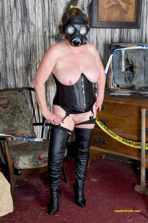 Hot old chick with a gas mask bares her huge breasts in black corset, fishnet stocking and boots before she sits on a silver steps and reveals pussy. - XXXonXXX - Pic 2