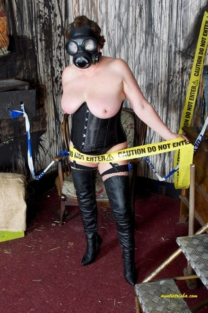 Hot old chick with a gas mask bares her huge breasts in black corset, fishnet stocking and boots before she sits on a silver steps and reveals pussy. - XXXonXXX - Pic 5