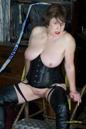 Hot old chick with a gas mask bares her huge breasts in black corset, fishnet stocking and boots before she sits on a silver steps and reveals pussy. - XXXonXXX - Pic 12