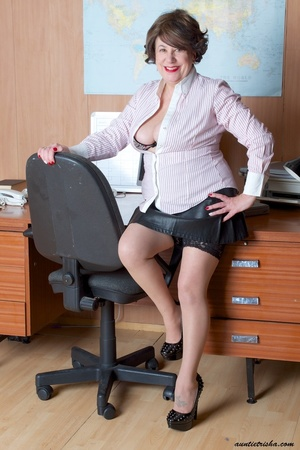 Mature secretary takes off her pink and white stripe polo and black skirt then displays her fat body in the office before she strips off her black, white and red underwear and bares her huge tits and hot pussy wearing her black, white and red corset and black high heels while sitting on her desk. - XXXonXXX - Pic 1