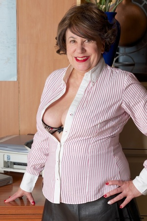 Mature secretary takes off her pink and white stripe polo and black skirt then displays her fat body in the office before she strips off her black, white and red underwear and bares her huge tits and hot pussy wearing her black, white and red corset and black high heels while sitting on her desk. - XXXonXXX - Pic 2