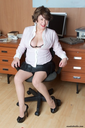 Mature secretary takes off her pink and white stripe polo and black skirt then displays her fat body in the office before she strips off her black, white and red underwear and bares her huge tits and hot pussy wearing her black, white and red corset and black high heels while sitting on her desk. - XXXonXXX - Pic 4