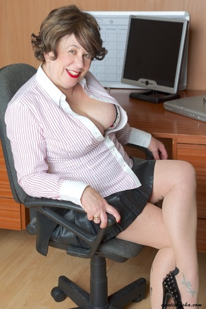 Mature secretary takes off her pink and white stripe polo and black skirt then displays her fat body in the office before she strips off her black, white and red underwear and bares her huge tits and hot pussy wearing her black, white and red corset and black high heels while sitting on her desk. - XXXonXXX - Pic 7