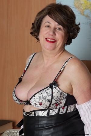Mature secretary takes off her pink and white stripe polo and black skirt then displays her fat body in the office before she strips off her black, white and red underwear and bares her huge tits and hot pussy wearing her black, white and red corset and black high heels while sitting on her desk. - XXXonXXX - Pic 11