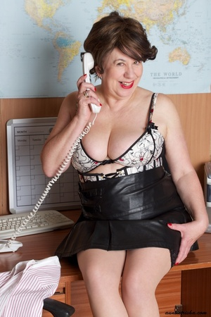 Mature secretary takes off her pink and white stripe polo and black skirt then displays her fat body in the office before she strips off her black, white and red underwear and bares her huge tits and hot pussy wearing her black, white and red corset and black high heels while sitting on her desk. - XXXonXXX - Pic 12