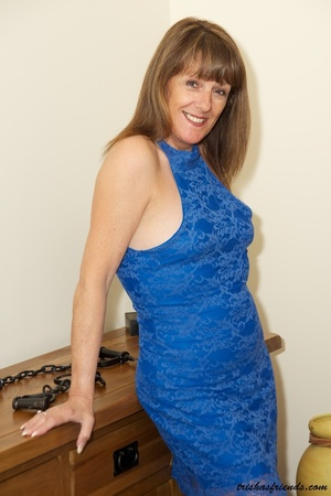 Hot cougar in blue dress and high heels slowly gets naked and displays her mature tits and butt by her wooden drawer. - XXXonXXX - Pic 1