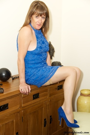 Hot cougar in blue dress and high heels slowly gets naked and displays her mature tits and butt by her wooden drawer. - XXXonXXX - Pic 9