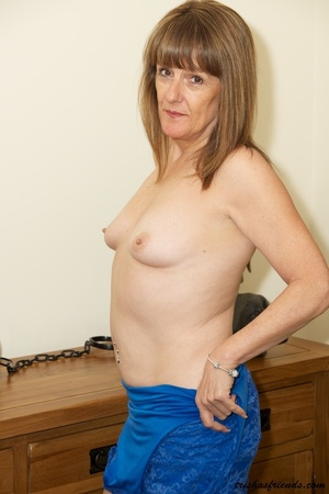 Hot cougar in blue dress and high heels slowly gets naked and displays her mature tits and butt by her wooden drawer. - XXXonXXX - Pic 15