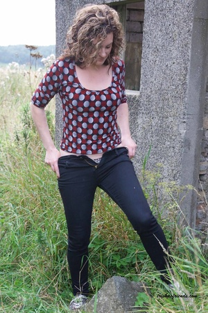 Gorgeous cougar in red and gray polka dotted shirt pulls down her blue jeans and white and black spotted panty and lets you peek at her hairy pussy outdoor. - XXXonXXX - Pic 4