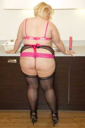 Mature fattie in pink lingerie, black stockings and high heels licks and sucks a huge black dildo before she sits on it while mashing her huge boobs by the kitchen sink. - XXXonXXX - Pic 1