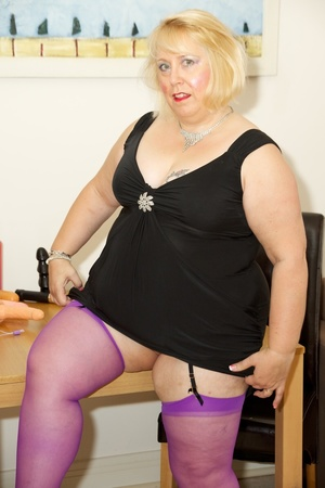 Fat mature babe sucks a pink dildo wearing her black dress, purple stockings and high heels before she takes off her dress and strips down her black bra then display her tits on a brown bed. - XXXonXXX - Pic 3