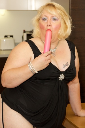Fat mature babe sucks a pink dildo wearing her black dress, purple stockings and high heels before she takes off her dress and strips down her black bra then display her tits on a brown bed. - XXXonXXX - Pic 7