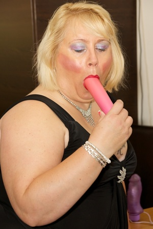 Fat mature babe sucks a pink dildo wearing her black dress, purple stockings and high heels before she takes off her dress and strips down her black bra then display her tits on a brown bed. - XXXonXXX - Pic 8