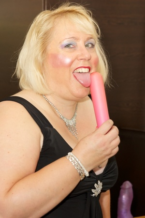 Fat mature babe sucks a pink dildo wearing her black dress, purple stockings and high heels before she takes off her dress and strips down her black bra then display her tits on a brown bed. - XXXonXXX - Pic 9