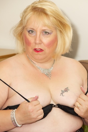 Fat mature babe sucks a pink dildo wearing her black dress, purple stockings and high heels before she takes off her dress and strips down her black bra then display her tits on a brown bed. - XXXonXXX - Pic 13