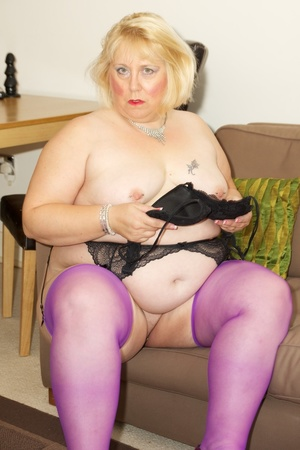 Fat mature babe sucks a pink dildo wearing her black dress, purple stockings and high heels before she takes off her dress and strips down her black bra then display her tits on a brown bed. - XXXonXXX - Pic 15