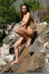 Chick shows her naked body on the rocks by a…