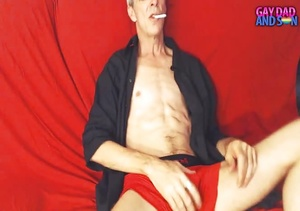Old dude lays down and smokes a cigarette on a red bed wearing a black robe before he pulls his big cock out of his red and black brief. - XXXonXXX - Pic 2