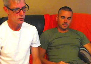 Mature dude with glasses wearing white shirt and a hot stud in green shirt both get naked then eats each others dicks in sixty-nine positions on a blue leather couch. - XXXonXXX - Pic 1