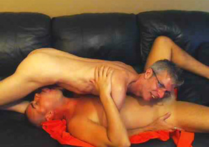 Mature dude with glasses wearing white shirt and a hot stud in green shirt both get naked then eats each others dicks in sixty-nine positions on a blue leather couch. - XXXonXXX - Pic 3