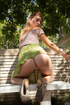 Dirty fair-haired teen in a short green skirt in sexy poses outdoors