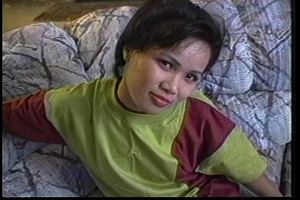 Filipina hottie sits on a gray couch wearing her green and brown shirt, black leggings and white rubber shoes then talks about doing some nude modelling. - XXXonXXX - Pic 1