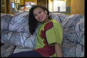 Filipina hottie sits on a gray couch wearing her green and brown shirt, black leggings and white rubber shoes then talks about doing some nude modelling. - XXXonXXX - Pic 2