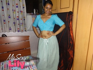 Luscious Indian hottie displays her chubby body before she opens her hanging blue blouse and reveals her big soft breasts then pulls down her white skirt and expose her huge juicy butt in her bedroom. - XXXonXXX - Pic 1