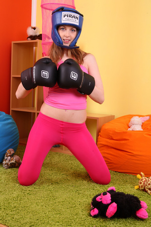 Teen hottie wearing blue head gear and black boxing gloves displays her hot body in sexy pink shirt and leggings before she slowly gets naked on an orange bean bag then reveals her small tits and indulging pussy. - XXXonXXX - Pic 2