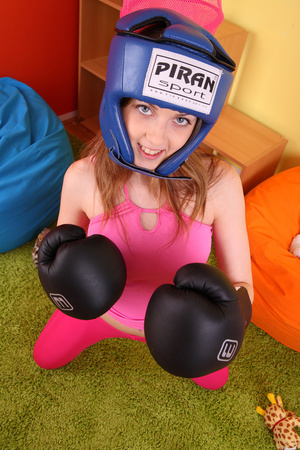 Teen hottie wearing blue head gear and black boxing gloves displays her hot body in sexy pink shirt and leggings before she slowly gets naked on an orange bean bag then reveals her small tits and indulging pussy. - XXXonXXX - Pic 3