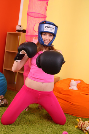 Teen hottie wearing blue head gear and black boxing gloves displays her hot body in sexy pink shirt and leggings before she slowly gets naked on an orange bean bag then reveals her small tits and indulging pussy. - XXXonXXX - Pic 5
