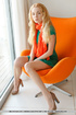 Welcoming chica in a green dress and panties strips on an orange chair.
