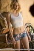 Fine strumpet in a white midriff top and denim shorts sits her bare ass