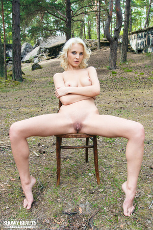 Blonde bombshell sits on a brown wooden chair outdoor then teases with her luscious body as she strips off her blue sweater and reveals her indulging boobs and pussy. - XXXonXXX - Pic 11