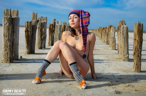 Pretty brunette wearing multi-colored bonnet planking by the beach in her blue shirt and green stockings before she gets naked and bares her stunning body with luscuous pussy in different poses wearing her black and white striped socks and orange slippers. - XXXonXXX - Pic 9