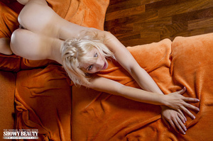 Blonde bombshell seduces with her alluring body in red lingerie before she slowly gets naked and reveals her soft tits and indulging pussy as she spreads her legs wide in different poses on an orange couch. - XXXonXXX - Pic 19